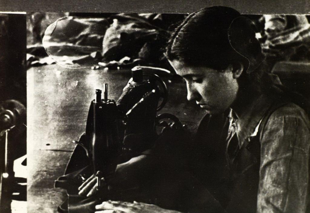 Комсомолка А.Габдрахманова – машинистка 1-ой Меховой фабрики выполняет заказ фронту. 1941