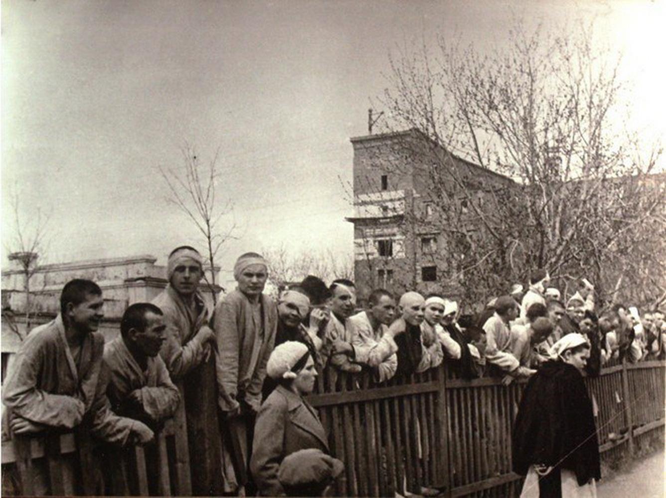 Раненные бойцы наблюдают за празднованием Дня Победы 9 мая 1945 года