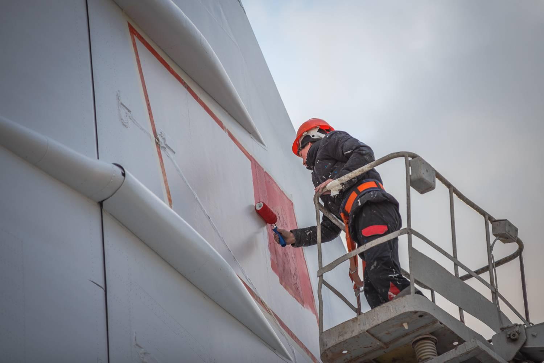 Специалист по покраске наносит изображение советского флага на самолет Ту-144. Фото: Владимир Васильев